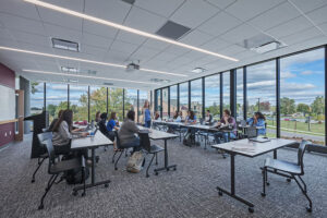 A professor teaches a large group of students in a classroom featuring floor to ceiling windows that overlook campus