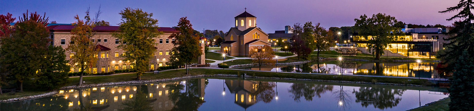 Pope John Paul II Center, St. Francis Chapel, and Achatz Hall of Science on a cloudless night reflecting in Mirror Lake