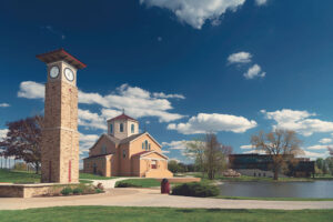 The St. Francis Chapel and clocktower on a sunny day with white puffy clouds in the sky