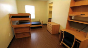 Undecorated room in Clare Hall with 2 beds, dressers, desks, and chairs