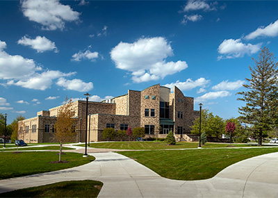 Doermer Health Sciences Center on a sunny day with cumulus clouds in the sky