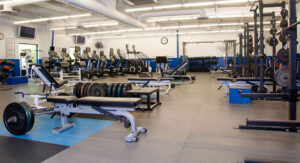 The fitness center has a variety of equipment to work with including squat racks, free weights, stationary bikes, treadmills, and weight machines.