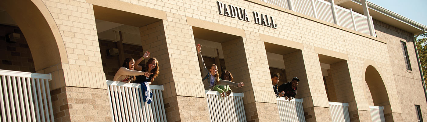 USF students waving and smiling on the balcony of Padua Hall.