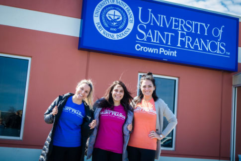 Three USF Crown Point students standing in front of the Crown Point building