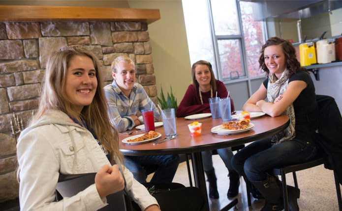 4 students smiling at the camera while eating lunch in Trinity's dining hall