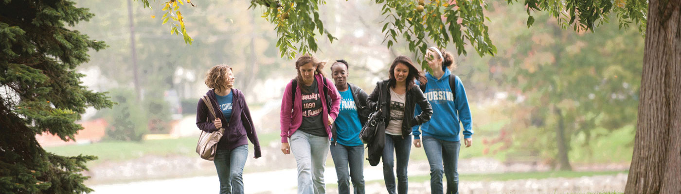 Nursing students walking to class along the path near JPII and the Doermer Health Sciences Center